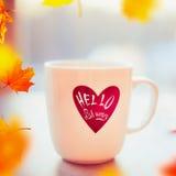 Tasse de thé ou de café sur la fenêtre toujours avec l'automne en baisse de feuilles et de textes d'automne bonjour Images libres de droits