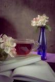 Tasse de thé près des livres et branches de fleur de pommier Photographie stock libre de droits
