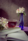 Tasse de thé près des livres et branches de fleur de pommier image stock