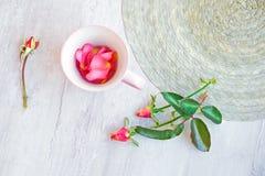 Tasse de thé rose avec des pétales de rose Photos stock