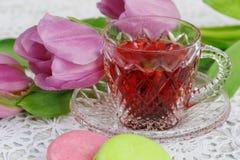 Tasse de thé rouge de karkadeh avec des macarons et des tulipes photo libre de droits
