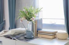 Tasse de thé sur le livre avec le vase de la fleur sur le bureau blanc Image stock