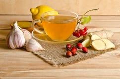 Tasse de thé, tranches de gingembre, miel, baies de cynorrhodon et viburnum images libres de droits
