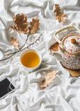 Tasse de thé vert, écouteurs, joueur, théière dans le lit, vue supérieure Matin paresseux, humeur chaude d'automne Photos stock