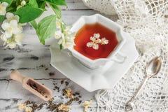 Tasse de thé vert avec des fleurs de jasmin Images stock