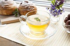 Tasse de thé vert avec le baume de citron et les petits pains savoureux Photos stock