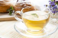 Tasse de thé vert avec le baume de citron et les petits pains savoureux Images stock
