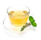 Tasse de thé vert avec les feuilles en bon état et la fleur photo libre de droits