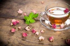 Tasse de thé vert avec les roses en bon état et sèches photographie stock