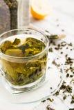 Tasse de thé vert et citron et cuillère sur une table en bois Photographie stock libre de droits