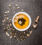 Tasse de thé de jasmin, de vieux scoop en bois et de fleurs fraîches sur le fond en pierre foncé Photographie stock libre de droits