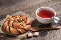 Tasse de thé et petit pain doux Photographie stock