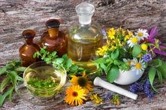 Tasse de tisane avec les bouteilles médicinales et les herbes curatives dans le MOIS Photos libres de droits