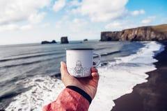Tasse de touristes à disposition avec l'image des montagnes sur le fond de la mer images stock