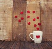 Tasse de Valentine avec des coeurs sur le fond en bois Image stock