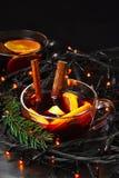 Tasse de vin chaud du ` s de nouvelle année avec l'orange et un bâton de cannelle avec une guirlande image stock