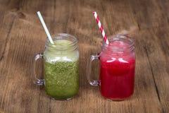 Tasse deux en verre de secousse de smoothie de jus d'aneth, de brocoli, de banane et de framboise sur le fond en bois, fin  Photo libre de droits
