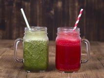 Tasse deux en verre de secousse de smoothie de jus d'aneth, de brocoli, de banane et de framboise sur le fond en bois, fin  Image stock