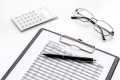 Tasse di paga per l'affare sullo scrittorio del lavoro d'ufficio con i vetri ed il fondo bianco del calcolatore fotografie stock libere da diritti