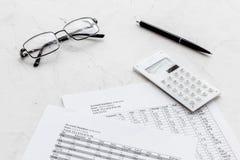 Tasse di paga per l'affare sullo scrittorio del lavoro d'ufficio con i vetri ed il fondo bianco del calcolatore immagine stock libera da diritti