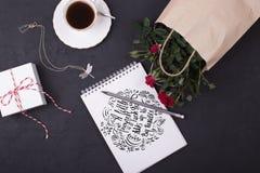Tasse du blanc de papier de café noir et de carnet avec la citation : Allumé Photos stock
