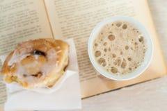 Tasse du café et du livre mordus outre de Cinnabon Images stock