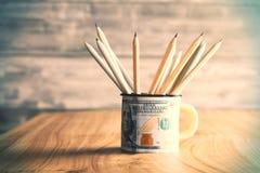 Tasse du dollar avec des crayons Images libres de droits