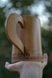 Tasse en bois sur la paume Photo stock