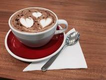 Tasse en céramique blanche avec la boisson chaude de café dans un plat rouge sur une table en bois Images stock