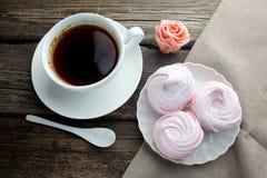Tasse en céramique blanche avec le dessert de café noir et de guimauve sur la table en bois, vue supérieure Image stock