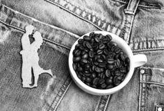 Tasse en c?ramique avec les grains de caf? et la silhouette en bois des couples de danse au-dessus du fond de denim Pause-caf? ro photo stock