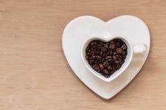 Tasse en forme de coeur avec des grains de café sur la table en bois Images libres de droits