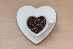 Tasse en forme de coeur avec des grains de café sur la table en bois Photographie stock libre de droits