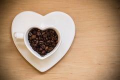 Tasse en forme de coeur avec des grains de café sur la table en bois Image stock