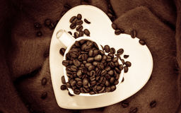 Tasse en forme de coeur avec des grains de café sur le brun Photographie stock libre de droits