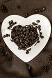 Tasse en forme de coeur avec des grains de café sur le brun Image libre de droits