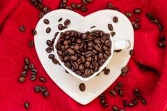 Tasse en forme de coeur avec des grains de café sur le rouge Photographie stock libre de droits