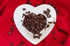 Tasse en forme de coeur avec des grains de café sur le rouge Image libre de droits