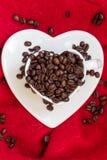Tasse en forme de coeur avec des grains de café sur le rouge Photographie stock