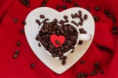 Tasse en forme de coeur avec des grains de café sur le rouge Images libres de droits