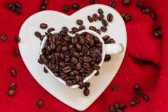 Tasse en forme de coeur avec des grains de café sur le rouge Images stock