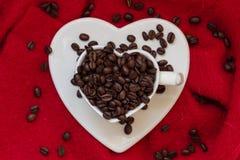 Tasse en forme de coeur avec des grains de café sur le rouge Image stock