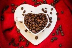 Tasse en forme de coeur avec des grains de café sur le rouge Photo stock