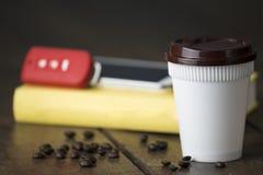 Tasse en plastique blanche de café chaud avec le chapeau brun et la clé et le mobi de voiture Photographie stock