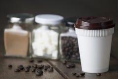 Tasse en plastique blanche de café chaud avec le pot de chapeau brun et trois en verre Image libre de droits