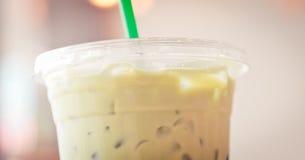 Tasse en plastique de matcha Iced avec la paille verte dans le ton crémeux image stock