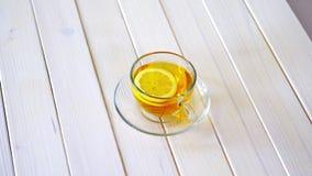 Tasse en verre avec le thé de chinois traditionnel et la tranche de citron sur la table blanche clips vidéos