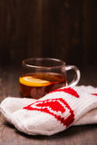 Tasse en verre avec le thé de citron et les mitaines tricotées Images stock