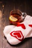Tasse en verre avec le thé de citron et les mitaines tricotées Photographie stock