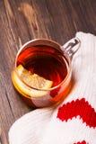 Tasse en verre avec le thé de citron et les mitaines tricotées Photo stock